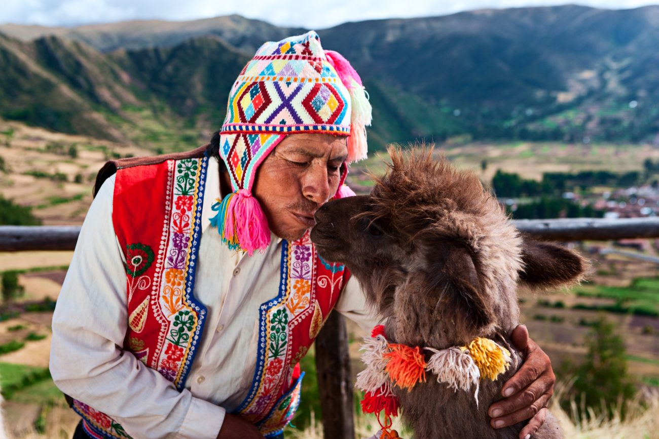 Peruvian man kissing llama near Pisac, Sacred Valley, Peru