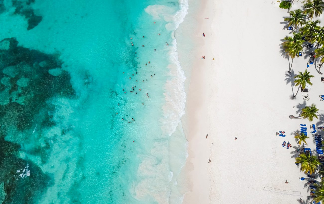 Incredible view of the white sandy beach from a bird's eye view. Top view of beautiful white sand beach with turquoise sea water and palm trees, aerial drone shot.