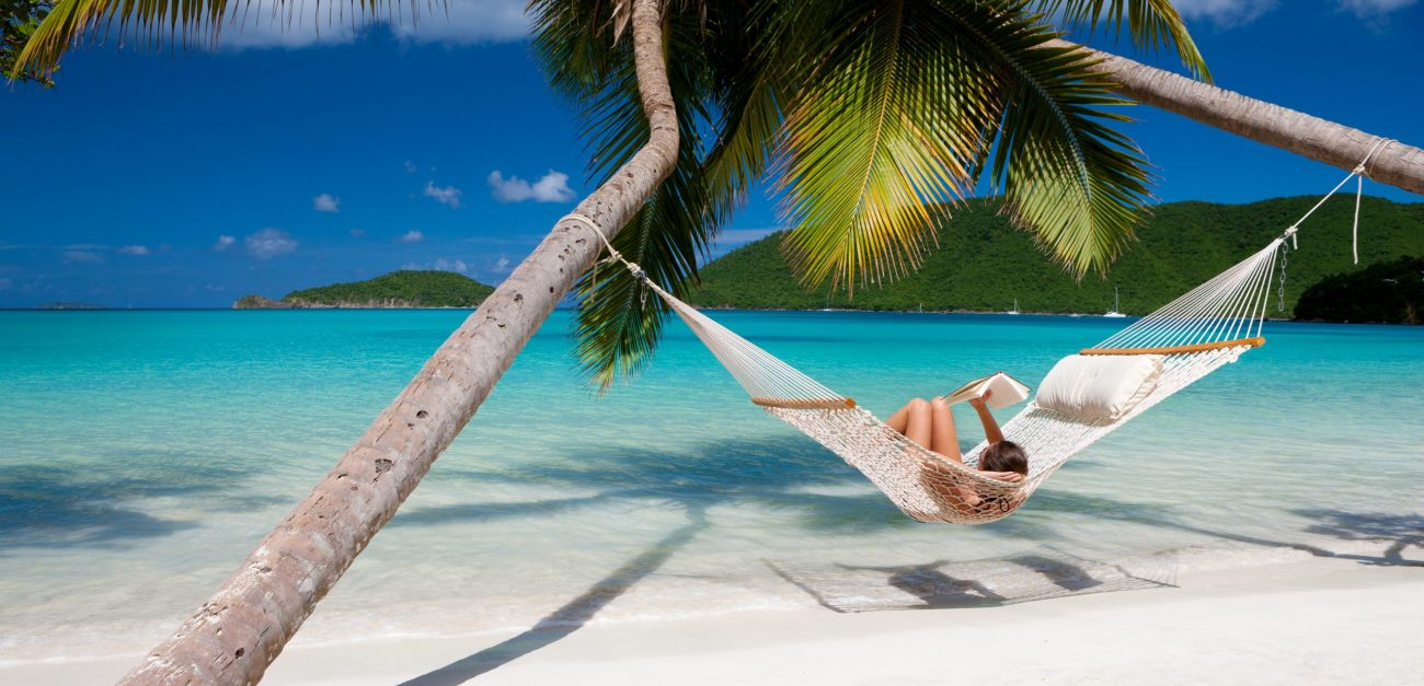 woman reading a book in hammock at the Caribbean beach